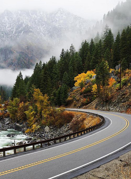 A section of U.S. Highway 2 next to the Wenatchee River with autumn color trees, firs, and snowy mountains in the background.